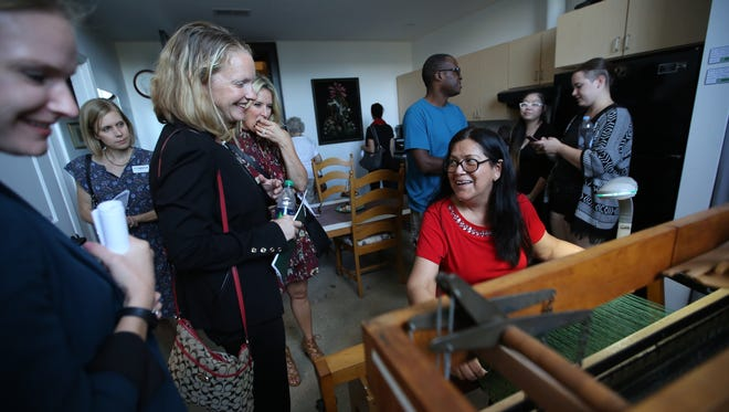 Fiber Artist Diana Leiva, 57, works on a loom and talks with Michele Wildman, Chief Housing Investment Officer for Michigan State Housing Development Authority during the open studio and live art demonstrations at the grand opening of the City Hall ArtSpace Lofts in Dearborn on Wednesday, Sept. 21, 2016.