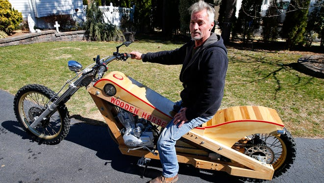 George Stempinski is shown with his functional wooden motocycle, believed to be the first of its kind in New Jersey, outside his Manahawkin home Wednesday, March 22, 2017.