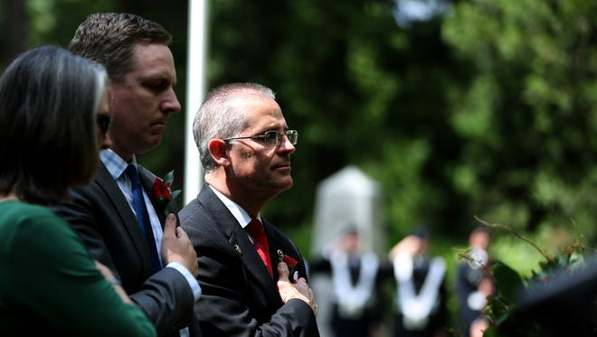 Wendall Pelham, right, Cameron Smith, the director of the Oregon Department of Veterans' Affairs, and Dawn Pelham, cover their hearts as taps is played during the Statewide Memorial Day Celebration organized by Oregon Department of Veterans' Affairs at the Afghan-Iraqi Freedom Memorial in Salem on Monday, May 29, 2017. The names of 142 Oregon service members who died in Afghanistan and Iraq, including the Pelhams' son John, are inscribed on the memorial wall.