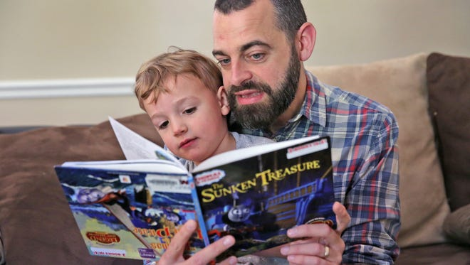 Adam Hayden reads with his son Noah at their Greenwood home, Tuesday, June 6, 2017.  He was diagnosed a year ago with brain cancer, glioblastoma multiforme.