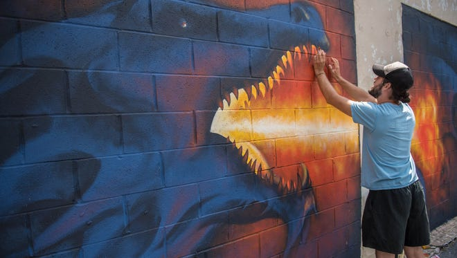 """David Eldred from Battle Creek works on a mural at Heritage Dry Cleaners, 146 North Ave., as part of the 2017 street art festival """"Color the Creek."""""""