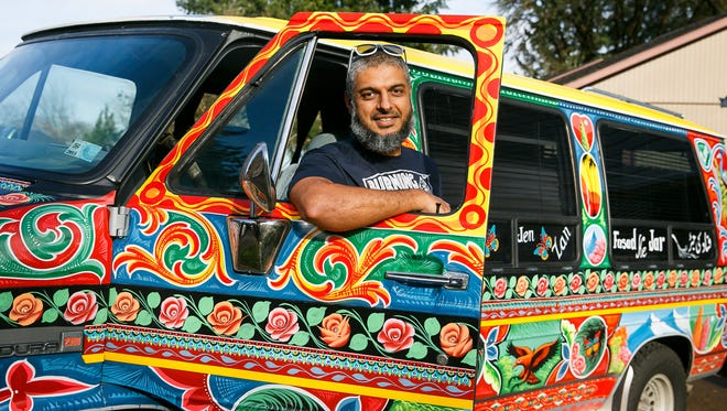 Fahd Saeed stands with his van that was painted by Pakistani artist Haider Ali in October. Saeed commissioned Ali, known as the Picasso of truck art, to paint his 1989 GMC Vandura.