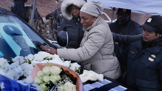 Nikole Flowers, center mourns the death of her son Detroit Police officer Glenn Doss at the end of a vigil at the 7th precinct in Detroit on Monday, January 29, 2017. Officer Doss died Sunday in the hospital days after being shot in the face while responding to a domestic call on Detroit's east side.