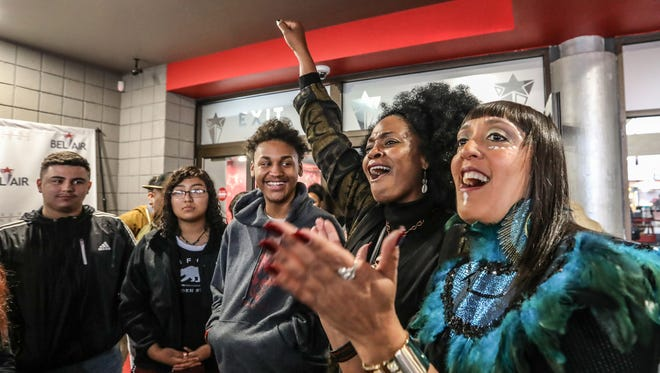 """Dorian Evans, 51, of Detroit,  lifts her fist in the air yelling """"Wakanda"""" as she welcomes students like Devon Anucinski, 17, of Detroit, left, to the VIP screening of Marvel's """"Black Panther"""" movie with the help of her friend Randa Davis, 51, of Inkster, right, at Bel Air Luxury Cinema in Detroit on Tuesday, Feb. 20, 2018. The screening for 160 Detroit high school students was made possible through the #DetroitBlackPantherChallenge that raised money through a Go Fund Me campaign."""
