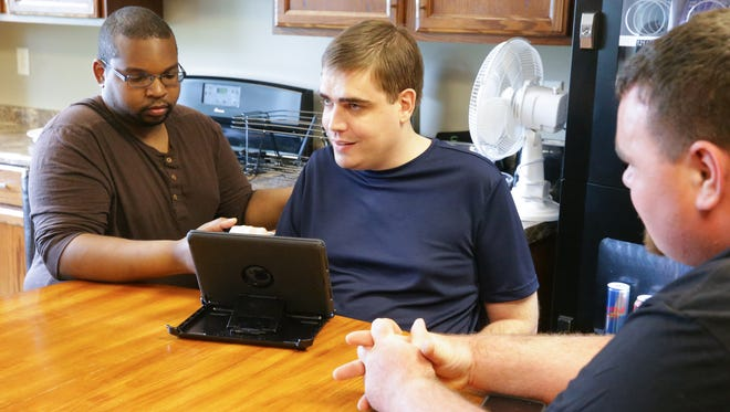 Direct Support Professional, Tim Davis, left, demonstrates how he helps Clayton Tharp to learn facilitated communication through an iPad, as client Rodney Phelps watches, at Insights Consulting in Indianapolis, Wednesday, May 9, 2018. Usually a Direct Support Professional would work with Clayton at his home. Insights Consulting provides support for individuals with intellectual and developmental disabilities, traumatic brain injury and autism spectrum disorders.