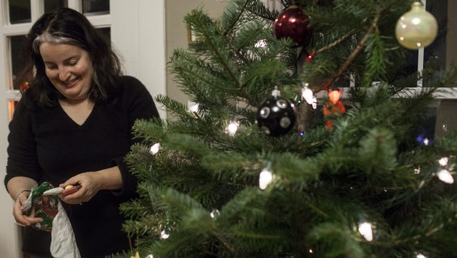 Jill Lightner decorates her Christmas tree at her Seattle home on Dec. 5.