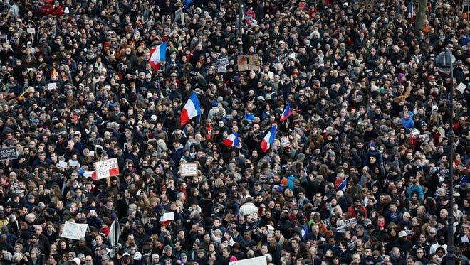 People gather at the Place de la Nation finishing point of a march to honor the victims of the terrorist attacks and to show unity, in Paris, France.