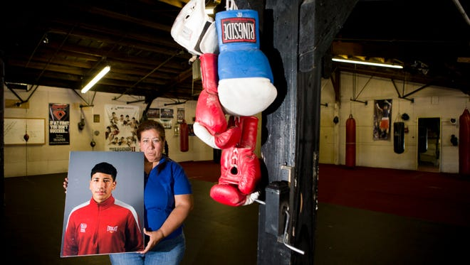 Consuelo Ochoa holds a photo of her son Alexis Urbina, a 17-year-old standout boxer who was murdered in 2013