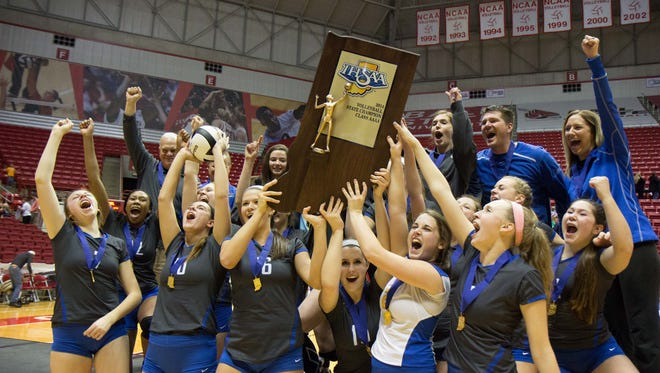 The Carmel girls volleyball team celebrate their state championship victory over Cathedral at Ball State, Nov. 8, 2014. Carmel won three games to two.