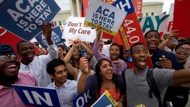 Students cheer as they hold up signs, outside of the Supreme Court on June 25, 2015, in Washington, supporting the Affordable Care Act after the Supreme Court decided that the ACA may provide nationwide tax subsidies.