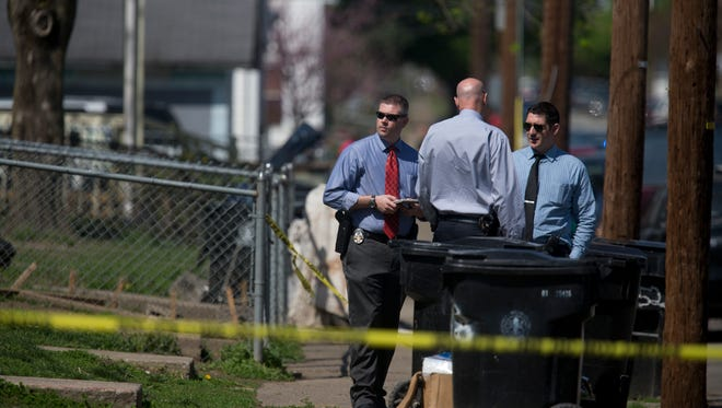 Louisville Metro police officers at the scene of a triple shooting on Rowan Street, betweeen 25th and 26th streets, in the Portland neighborhood. April 12, 2017.