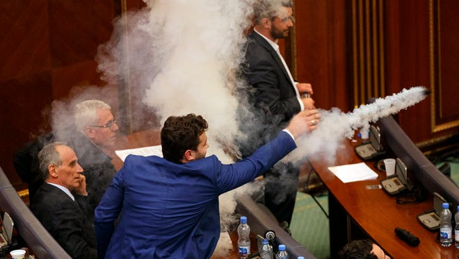 A Kosovo opposition lawmaker throws tear gas for the fourth time before the vote for agreement on border demarcation with Montenegro during a parliamentary session in Pristina, Kosovo, on March 21, 2018.