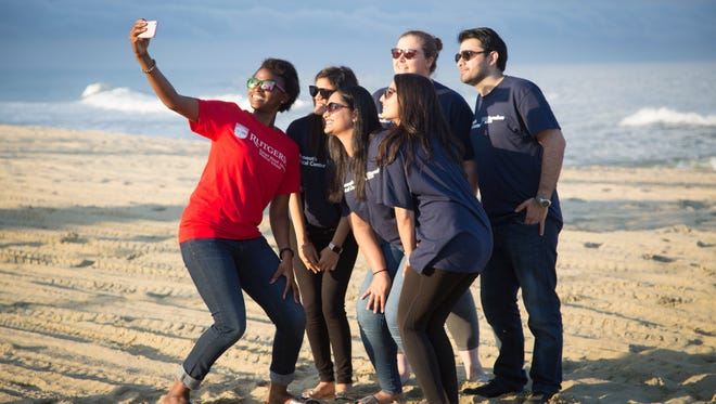 Rutgers Robert Wood Johnson Medical School student (l-r) takes a selfie with current residents at Monmouth Medical Center during a beach bonfire and barbecue event.