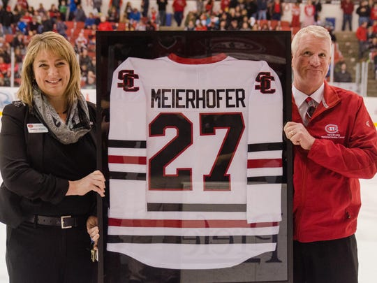 St. Cloud State director of athletics Heather Weems (left) presents Joe Meierhofer with a framed jersey last season to honor his 27 hockey seasons working at the Herb Brooks National Hockey Center. Meierhofer, who retired in June, is working as an ice technician at the 2018 Winter Olympics for figure skating and short track speed skating in South Korea.