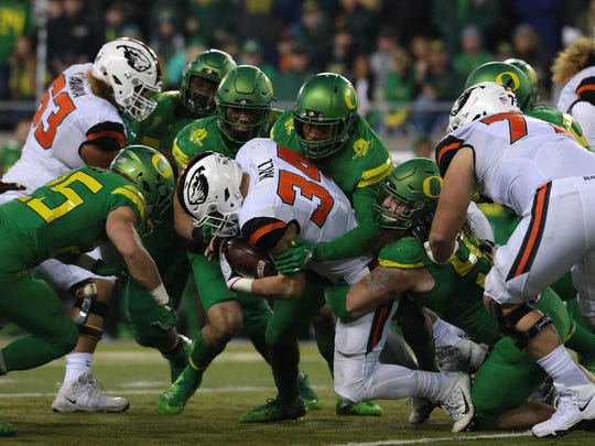 Nov 25, 2017; Eugene, OR, USA; Oregon State Beavers running back Ryan Nall (34) is tackled by Oregon Ducks defensive back Brady Breeze (25) and defensive lineman Jalen Jelks (97) and linebacker Troy Dye (35) and linebacker Justin Hollins (11) in the first half at Autzen Stadium. Mandatory Credit: Scott Olmos-USA TODAY Sports