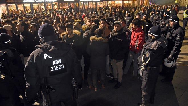 Police officers surround a group of men in front of the Cologne, western Germany, main station, on Dec. 31, 2016, where a string of robberies and sexual assaults last year were blamed largely on migrants from North Africa.