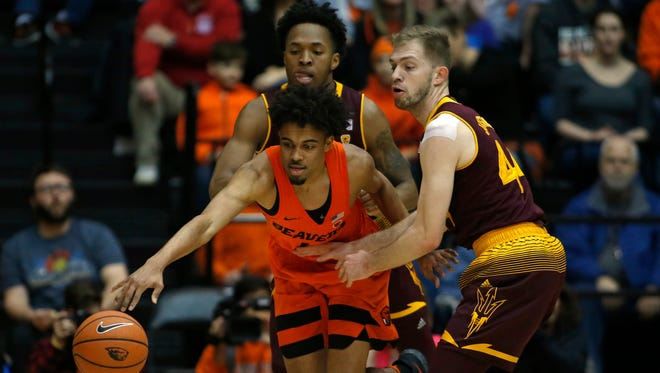 Oregon State's Stephen Thompson Jr., center, protects the ball from Arizona State's Kimani Lawrence, rear, and Kodi Justice, right, in the first half of an NCAA college basketball game in Corvallis, Ore., Saturday, Feb. 24, 2018.