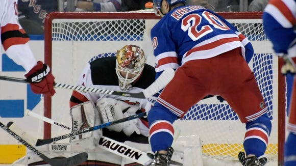 New Jersey Devils goalie Keith Kinkaid (1) covers up the puck as New York Rangers left wing Chris Kreider (20) looks for a rebound during the first period of an NHL hockey game Saturday, Dec. 9, 2017, at Madison Square Garden in New York. (AP Photo/Bill Kostroun)
