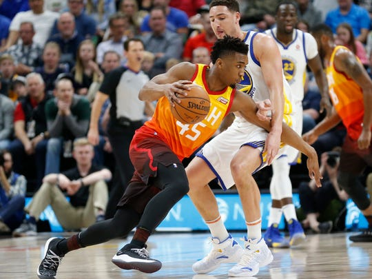 Utah Jazz guard Donovan Mitchell (45) drives around Golden State Warriors guard Klay Thompson, right, in the first half during an NBA basketball game Tuesday, Jan. 30, 2018, in Salt Lake City. (AP Photo/Rick Bowmer)