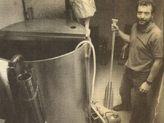 Jeff Lebesch stands with a mixing paddle next to a kettle in his basement brewery in 1991.