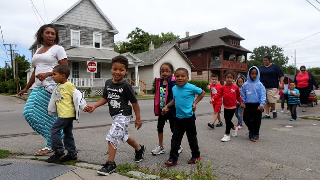 Tiffany Archibald leads Cesar Lora and Ezekiel Ortiz with the rest of her prekindergarten summer program students at Ibero Family Center to the library on Joseph Avenue. The summer learning program that targets Rochester School District students was expanded to prekindergarten this year with grant funding.