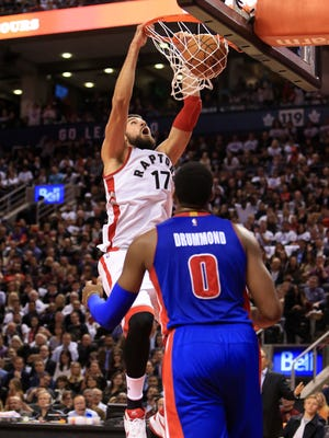 Raptors center Jonas Valanciunas dunks as Pistons center Andre Drummond looks on during the second half at Air Canada Centre on Oct. 26, 2016 in Toronto.