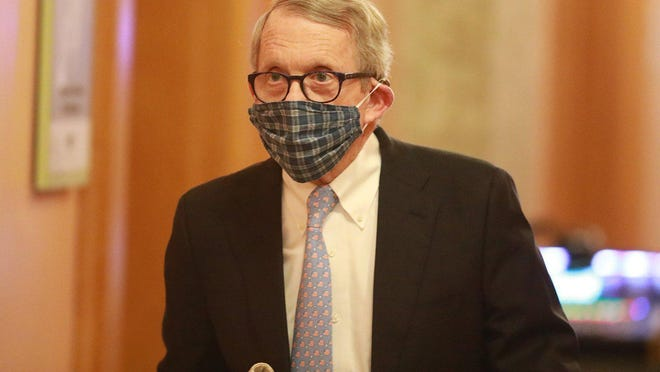 Wearing his protective mask made by his wife, Ohio Gov. Mike DeWine walks into his daily coronavirus news conference on Thursday, April 16, at the Ohio Statehouse in Columbus.