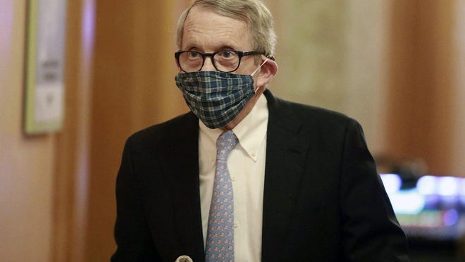 In this April 16, 2020, file photo wearing his protective mask made by his wife, Ohio Gov. Mike DeWine walks into his daily coronavirus news conference at the Ohio Statehouse in Columbus, Ohio.