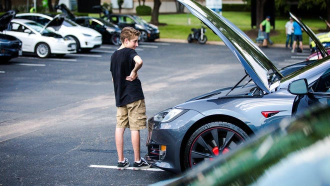 """Coleman Lyons looks in the hood of his father's Tesla Model S P100D, nicknamed """"Midnight Rider"""", at the Electric Vehicle Car Show and Expo last year."""