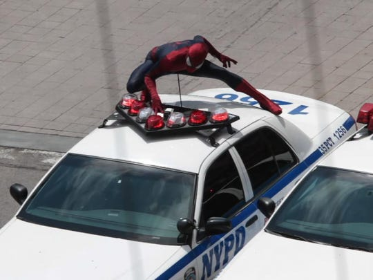Spider-Man rides on top of a New York City police car on Main Street heading west in downtown Rochester, during filming for The Amazing Spider-Man 2 in May 2013.