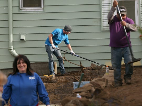 Volunteer Brad Storey, center, rakes next to the house as he and fellow volunteers work on the landscaping of the Community Frameworks home on Highland Avenue in Bremerton.