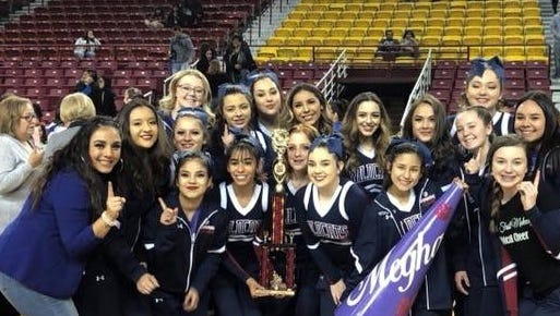 The Deming High Wildcat cheer team produly displays its first-place trophy at the NMSU Spirit Championships on Feb. 24 at the Pan-Am Center in Las Cruces.