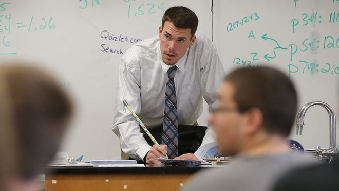 Minnesota Twins prospect Alex Meyer, a substitute teacher during the offseason, collects study guides during science class at Greensburg High School in Indiana.
