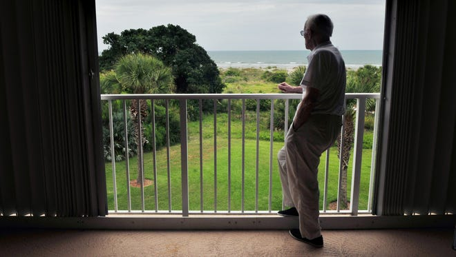 Jack Ensminger of Cape Canaveral, a World War II veteran, looks off the balcony of his beachfront condo as he reminisces.