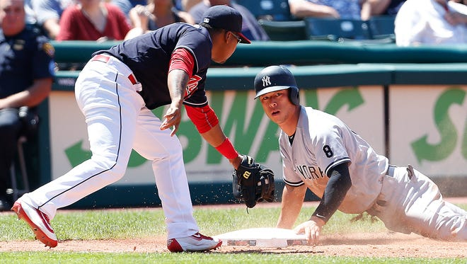 New York Yankees' Rob Refsnyder, right, is safe at third base after advancing on a single by Jacoby Ellsbury as Cleveland Indians' Jose Ramirez, left, covers the base during the fifth inning of a baseball game Sunday, July 10, 2016, in Cleveland.