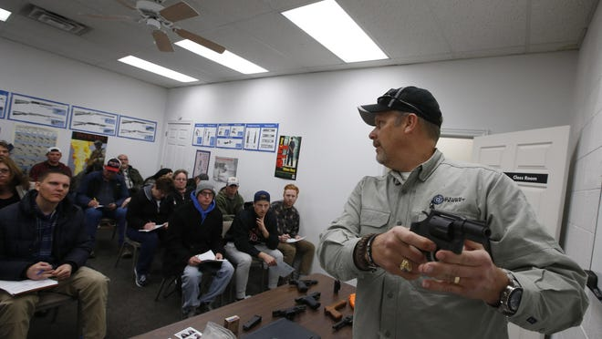 Gun instructor demonstrates an revolver as as he teaches a packed class to obtain the Utah concealed gun carry permit.
