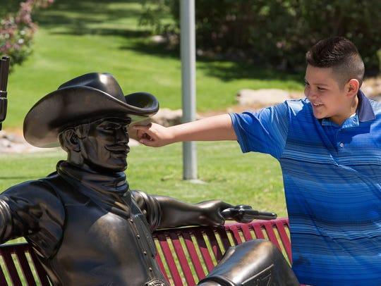Luis Torres, 11, moves slowly to poke the new bronze