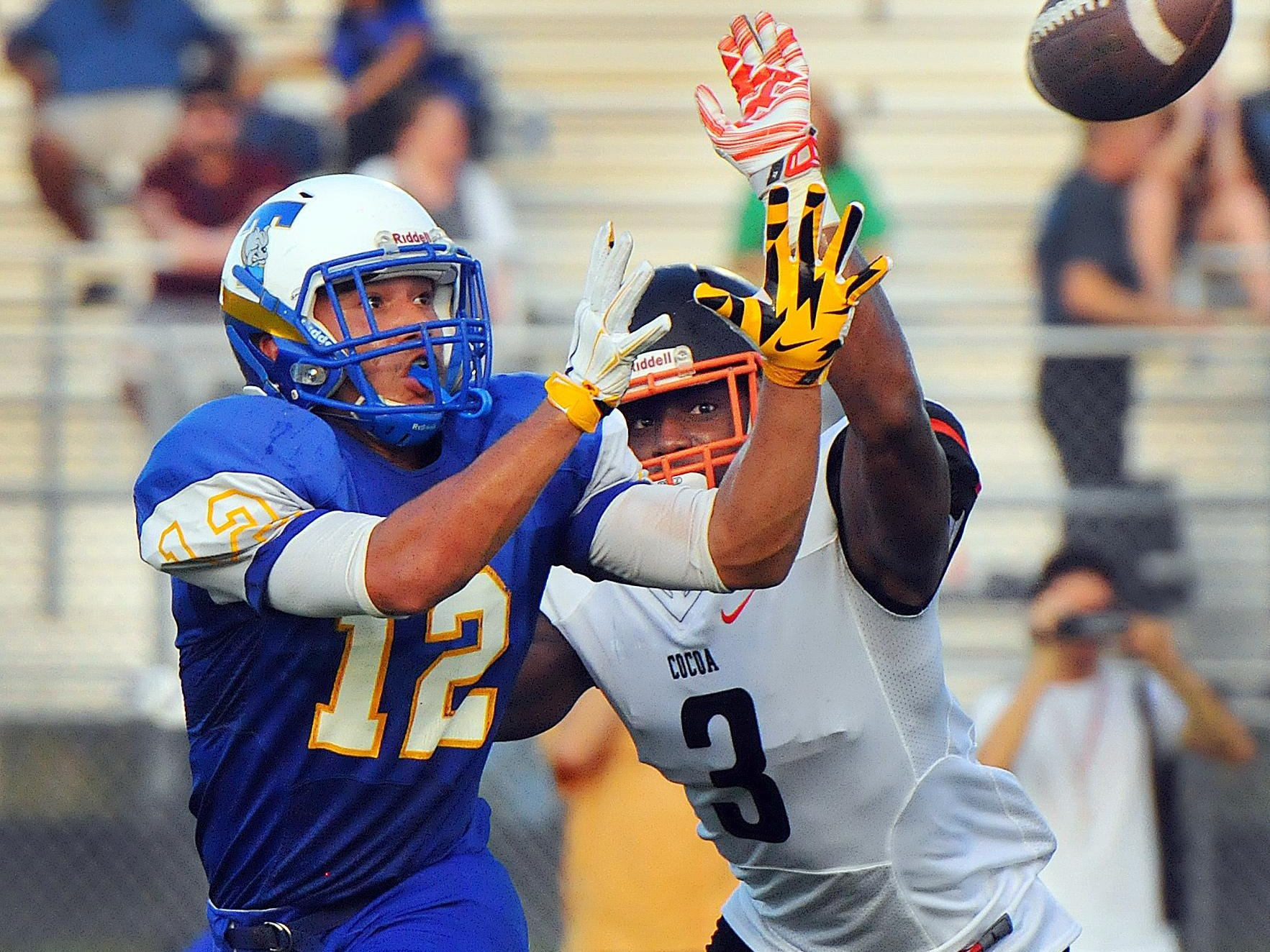 Titusville High's Tommy Mack (12) goes up for a catch with Cocoa High's Chauncey Gardner defending during Friday night's preseason game held at Titusville High. Cocoa won 38-13.