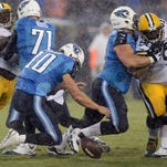 Titans quarterback Jake Locker (10) fumbles a wet football in the rain during the first quarter of Saturday's preseason game against the Packers at LP Field.