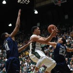 CSU guard Daniel Bejarano looks to pass to an open teammate after driving between Nevada defenders Eric Cooper (11) and Michael Perez during the Rams' 98-42 win over the Wolf Pack on Jan. 14 at Moby Arena.