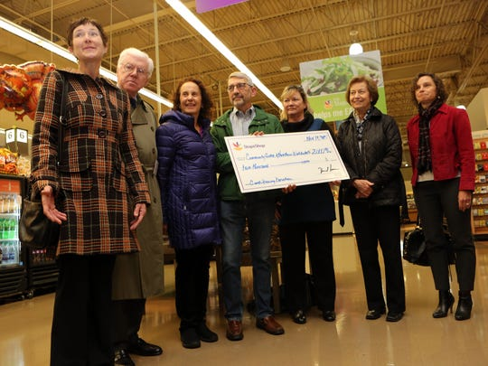 Clare Murray, left, the assistant director of the Katonah-based Community Center of Northern Westchester, thanks Stop & Shop for the $2,000 check that will help stock their food pantry during the store's grand opening in Mount Kisco, Nov. 19, 2015. The store was formerly an A&P supermarket.