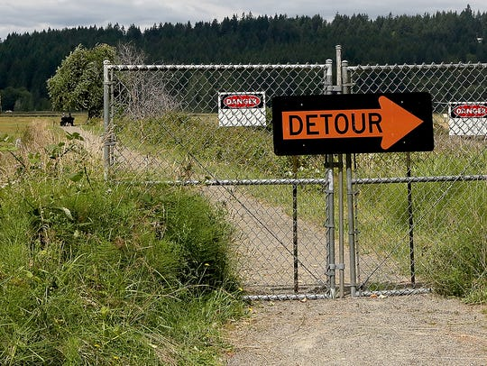 A gate and signs blocks the closed trail area at Mary E. Theler Wetlands in Belfair on Monday.