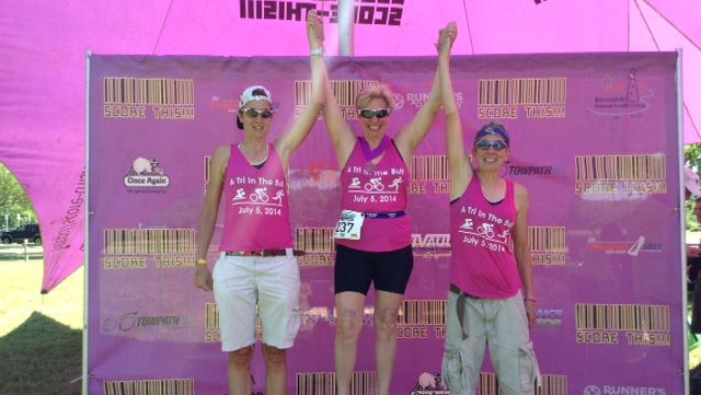 Jill Bates, center, took first place in her age group at the Runner's Remedy: A Tri in the Buff, in Buffalo on July 5, 2014.  She is flanked by her sister-in-law Elizabeth Bianchi, left, who placed 2nd in her age group, and her sister, Jody Mattulke, right,  who placed 3rd in her age group.