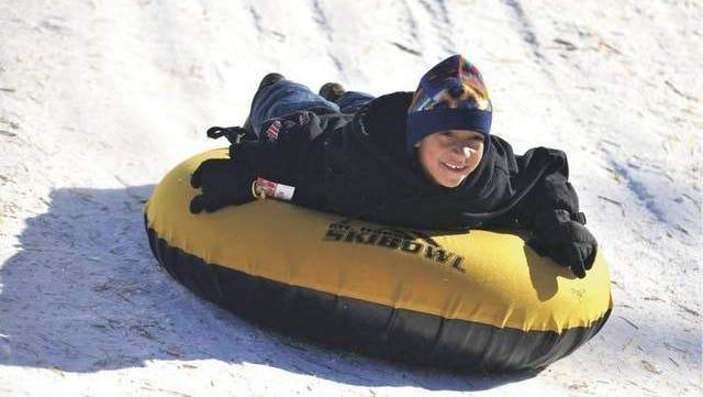 Elias Rufai, 7, grins as he slides down the mountain at Skibowl.