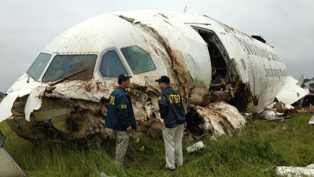 In this handout photo provided by the National Transportation Safety Board, NTSB workers inspect the wreckage of a UPS cargo plane that crashed in a field outside of Birmingham-Shuttlesworth International Airport August 14, 2013 in Birmingham, Alabama.