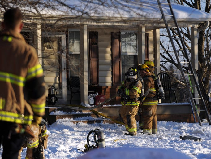 Firefighters pull a house from a house Thursday morning,