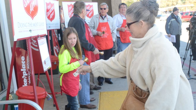 Susan Patrick (right) donates to the Salvation Army Red Kettle as bell ringer Emma Stracener, a Phoenix Elementary School pupil, looks on Friday. The Salvation Army officially kicked off the seasonal kettle bell program at Kmart on Military Highway in Pineville.