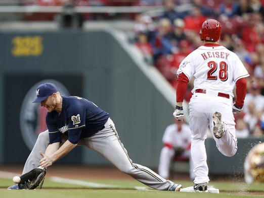 Reds left fielder Chris Heisey beats the throw as Brewers first baseman Lyle Overbay tries to scoop the ball.