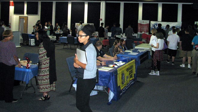 Job applicants visit employer tables at last year's Pennsauken job fair. Another fair is set for Thursday.