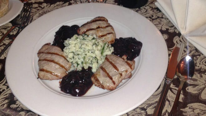 Pork tenderloin is plated with homemade spaetzle and cherry sauce.